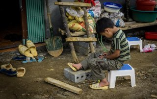 Un bambino che gioca con lo smartphone a Sapa