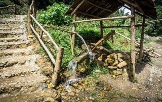 L'acqua che scorre in dei tronchi cavi, una fontana rudimentale