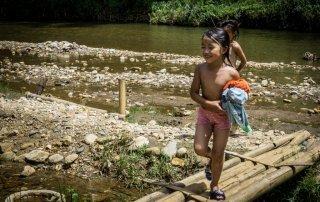 Una bimba che gioca e esce dal fiume in cui ha fatto il bagno