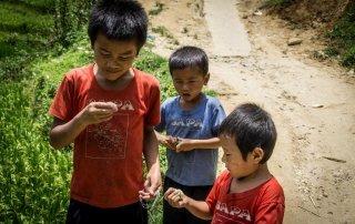 Tre bambini giocano con quel poco che hanno