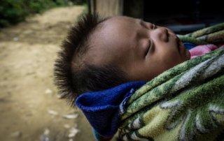 Un neonato viene trasportato in una coperta dalla mamma