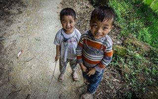 Due bambini in posa che portano strane collane di ferro, probabilmente simboli di appartenenza