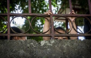 Un bambina da dietro un muro si sporge arreggendosi alla ringhiera