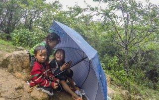 Tre bambine giocano con lo smartphone e si riparano sotto l'ombrello