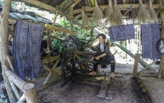 Una tessitrice tesse la canapa con un telaio interamente in legno