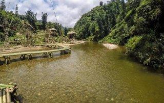 Un ponte costruito con canne di bambù attraversa il fiume del villaggio