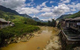 Il fiume marrone che scorre tra le case