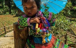 Bellissima bambina vestita con abiti locali si ripara dal sole con un ombrellino