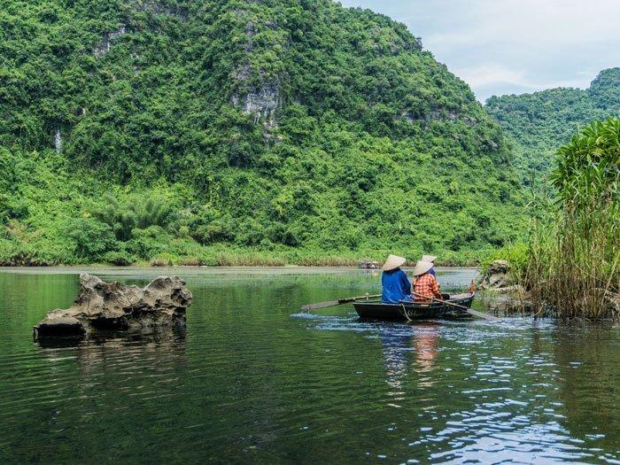 Foto sul fiume con una barca e tre persone con cappello vietnamita
