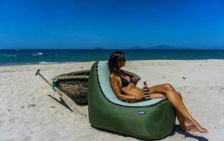Ragazza seduta su materassino gonfiabile in spiaggia con birra in mano