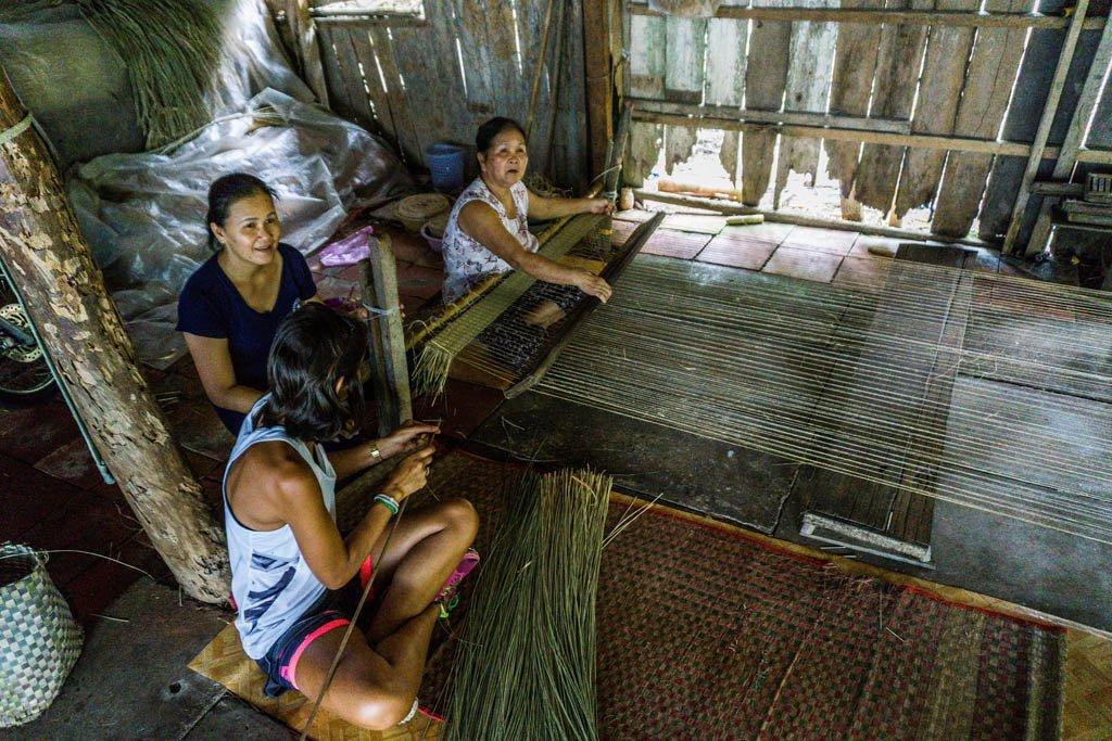 Due donne del posto che insegnano a Serena come fare i tappeti in bambù