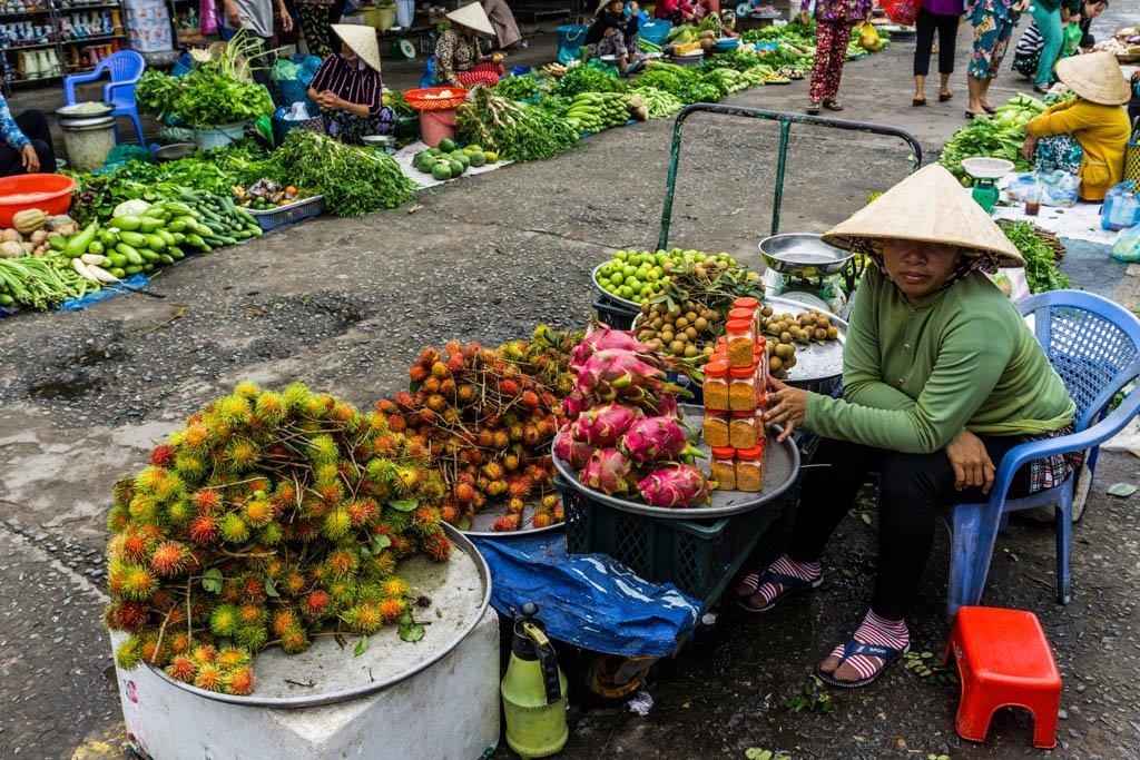 Donna al mercato con un banco ricco di frutta tropicale