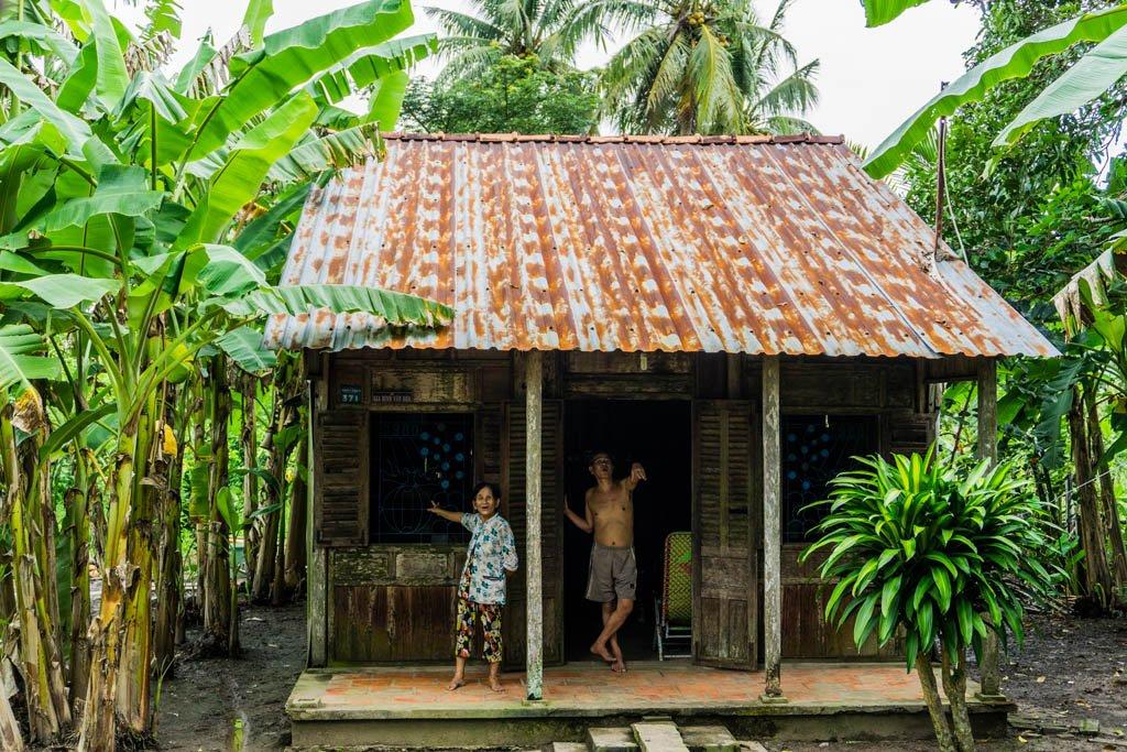 Casa nella giungla con uomo e donna vietnamiti sulla porta
