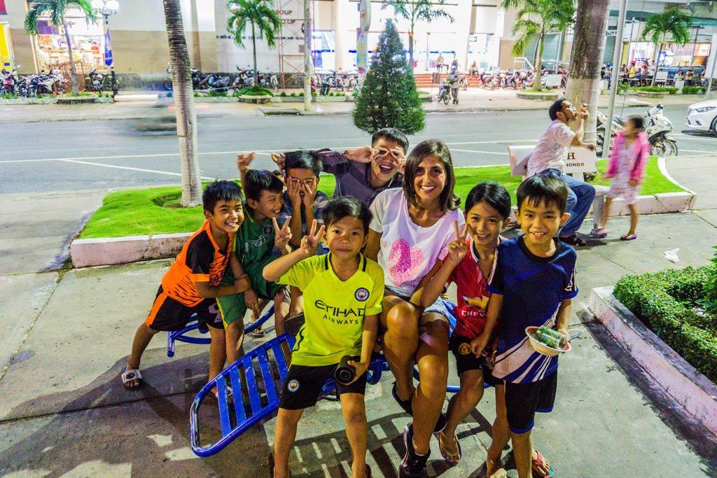 Serena seduta in una piazza circondata da bambini vietnamiti
