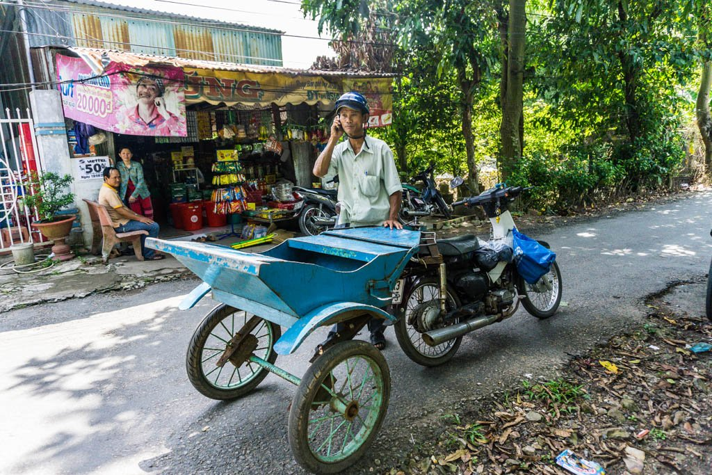 Signore vietnamita dietro allo xe loi, il tipico mezzo di trasporto del Delta del Mekong formato da moto e un carretto legato deitro