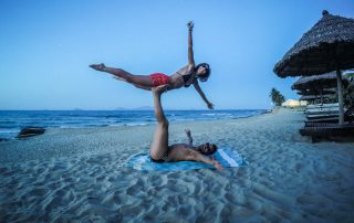 Ragazzo e ragazza in spiaggia che fanno acrobazie