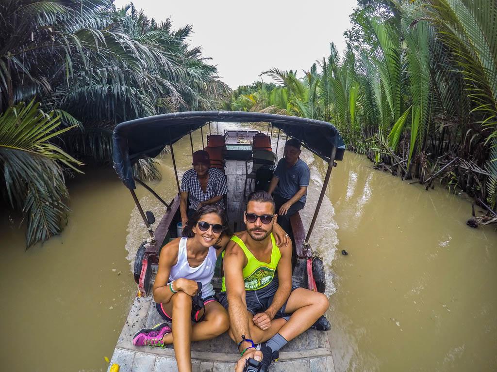 ragazzo ragazza e due signori vietnamiti che si scattano una foto sulla barca sul fiume