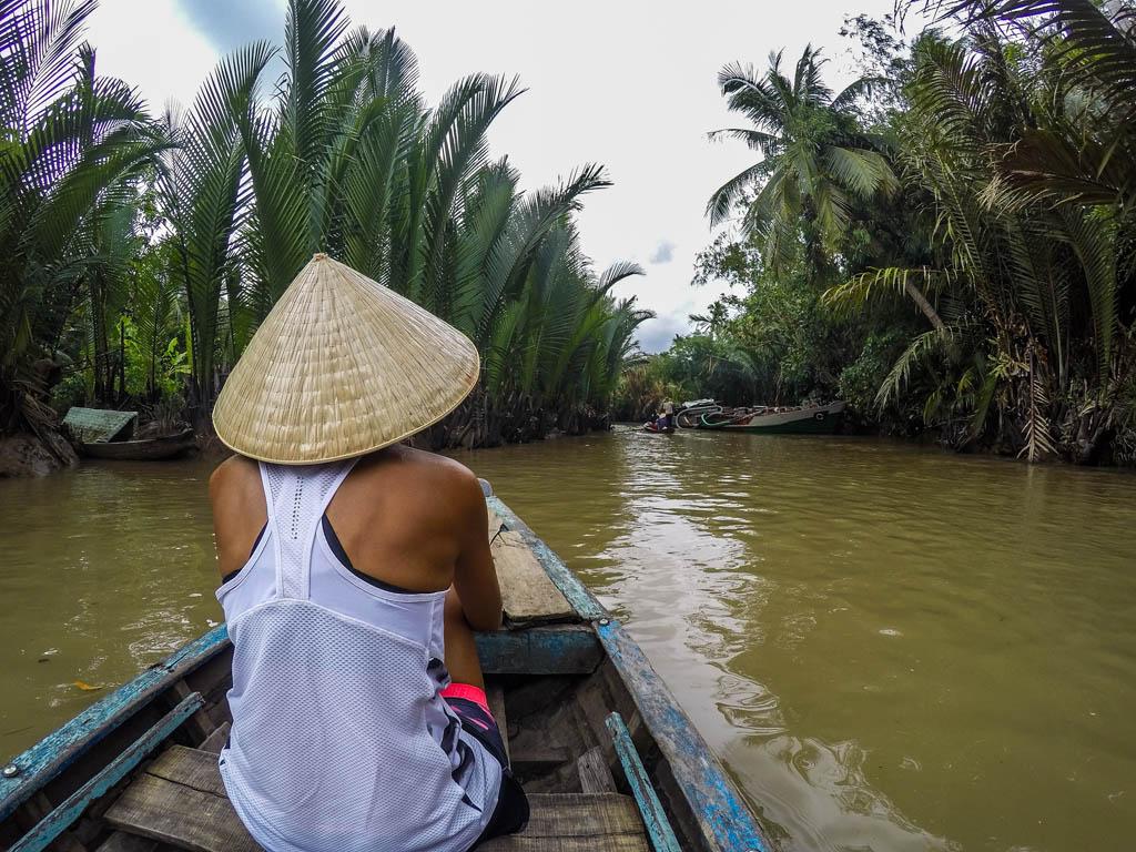 Ragazza di spalle su barca con cappello vietnamita