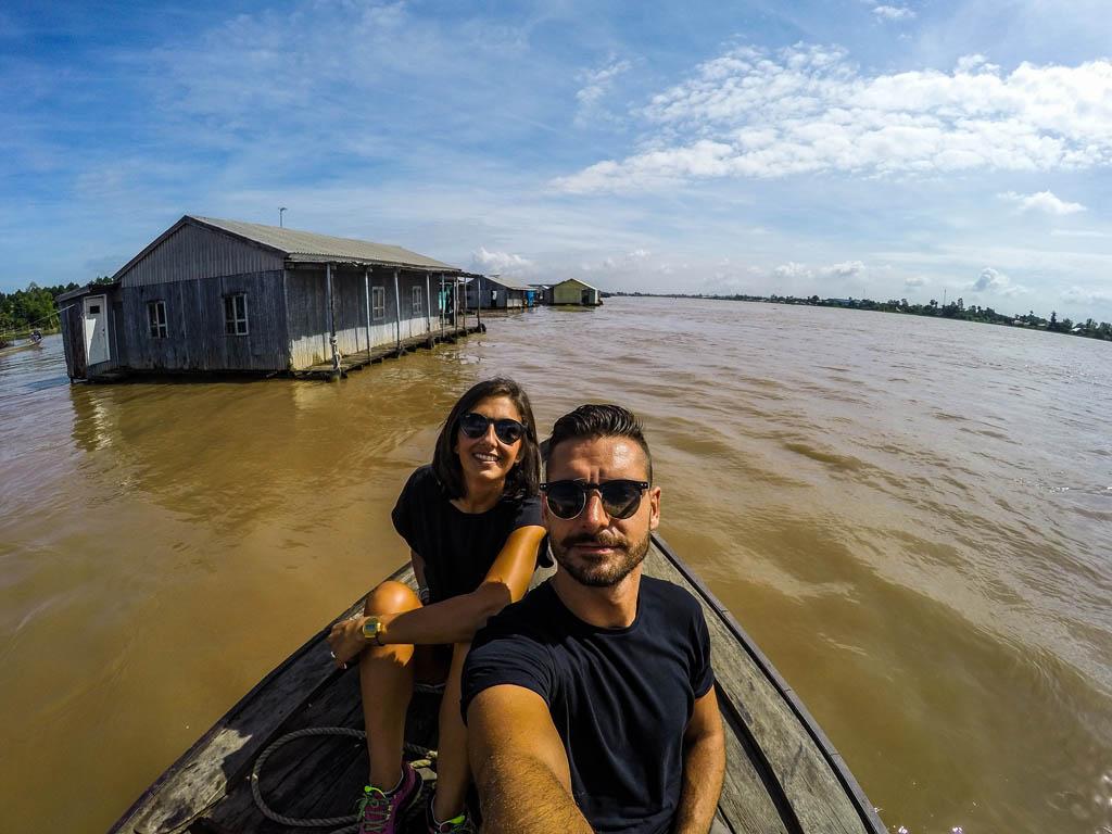 ragazzo e ragazza che si scattano una foto in barca sul fiume con le case galleggianti sullo sfondo