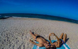 ragazzo e ragazza in spiaggia sdraiati sul telo in spiaggia davanti al mare