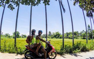 Ragazzo e ragazza in motorino davanti alle palme e al campo di riso