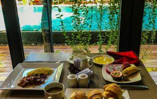 Tavolo imbandito per la colazione davanti alla piscina
