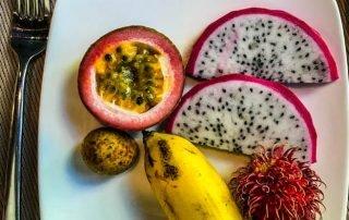 Piatto bianco su tavolo con Frutto della passione, frutto del drago, rambutan e mini banana