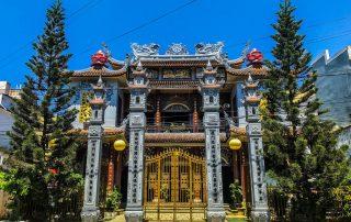 Edificio in stile cinese con colonne e decori, in mezzo a due abeti