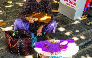 Anziana signora che vende ventagli seduta a sul marciapiede, sorridente e senza denti