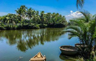 Vista del canale di Hoi An con barche tipiche legate alle canne di bamboo