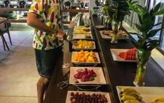 Francesco con la camicia con le stampe di frutta al bancone della frutta in hotel