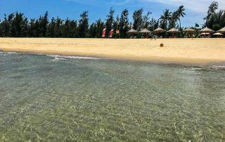 Vista dalle spiaggia dal mare con ombrelloni di legno sullo sfondo
