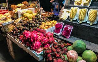 La frutta vietnamita colorata esposta su un banco del mercato