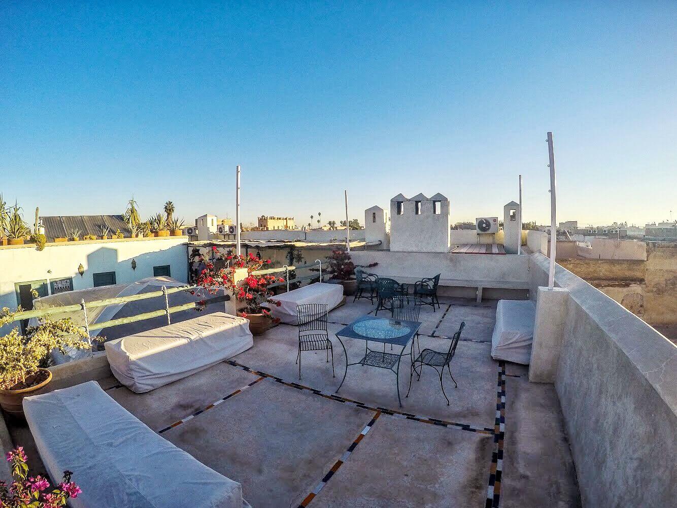 terrazza con tavolini e divani sul tetto di un Riad