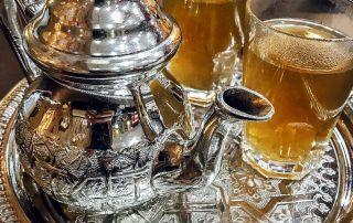 Teiera in argento e bicchieri riempiti di tè alla menta poggiati su un vassoio