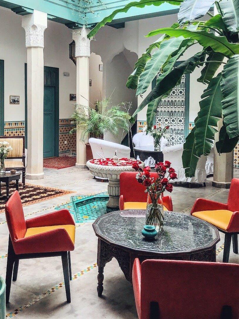 cortile interno di un riad con tavoli poltrone fontana e palme