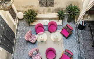 cortile interno di un riad ripreso dall'alto con le poltroncine rosa