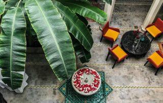 cortile di un riad visto dall'alto con poltrone, fontana e una palma