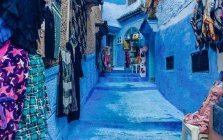 Strada dipinta di blu con scalini e abiti e tappeti appesi fuori dai negozi
