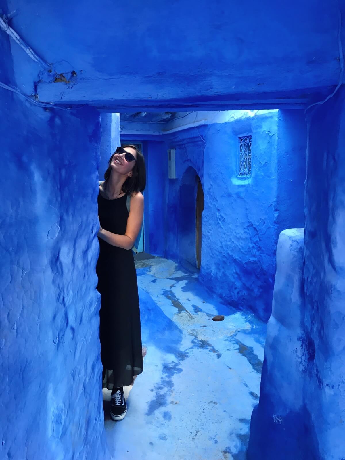 Ragazza vestita di nero nel mezzo di una strada tutta blu