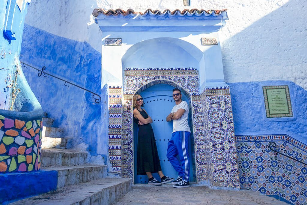 Serena e Francesco in posa davanti ad una porta blu di Chefchaouen