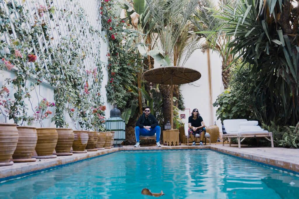 Ragazzo e ragazza fotografati in piscina seduti su una sedia al bordo