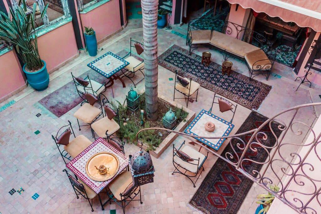 Cortile interno di un Riad con tavoli sedie e una palma al centro