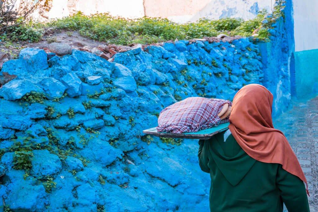Una donna che porta il pane tra le vie di Chefchaouen la città blu del Marocco