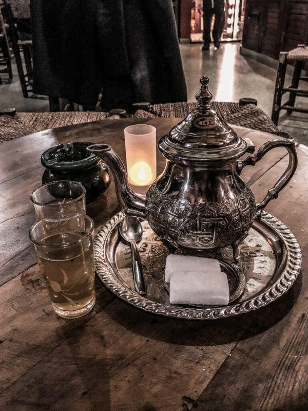 Una teiera d'argento dentro a un vassoio, poggiata su di un tavolo di legno