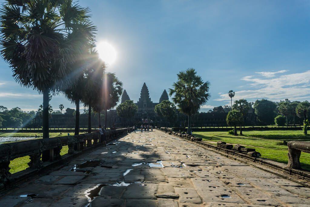 Via con pietre, palme di lato alla strada, grande parco e tempio sullo sfondo