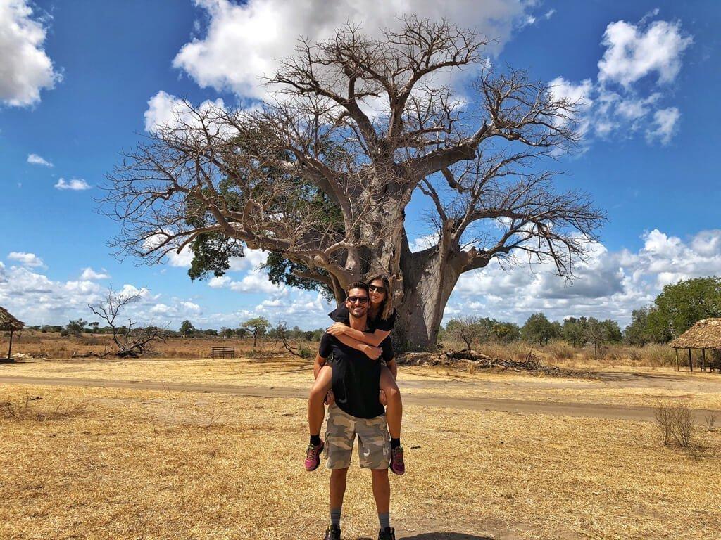 Ragazza in braccio ad un ragazzo davanti ad un grandissimo albero