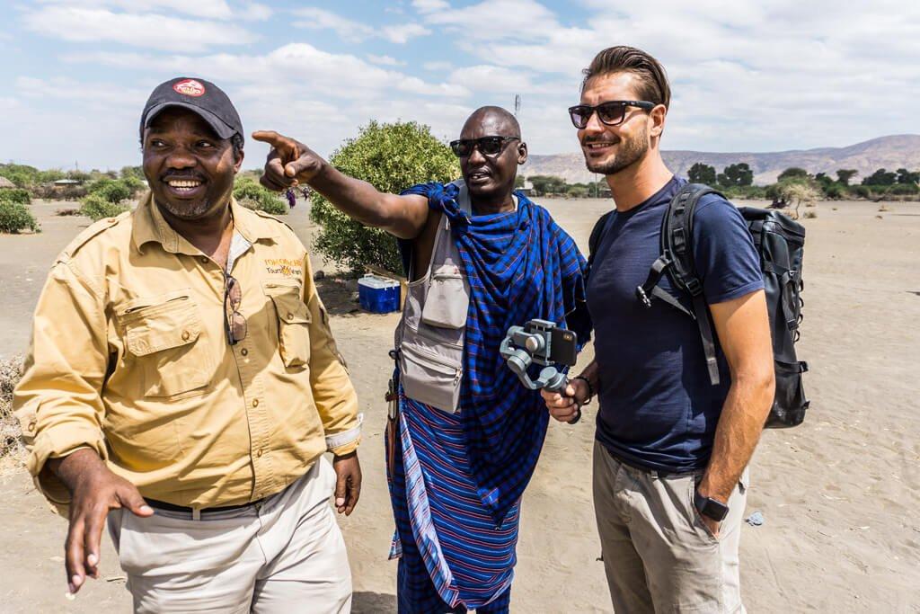 Ragazzo con due uomini africani dentro il villaggio Masai