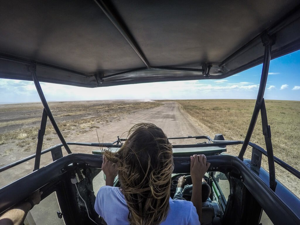 ragazza affacciata fuori dalla jeep su strada sterrata nella savana