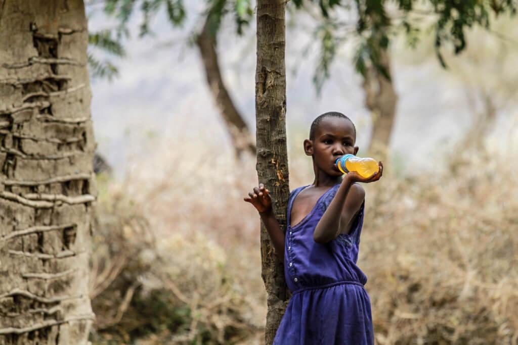 bambina Masai che beve una bottiglia di succo di frutta